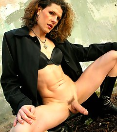 Tranny in a trench coat flashing her she-cock outside.
